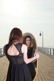 La mujer pensativa mira la reflexión en espejo Fotografía de archivo libre de regalías