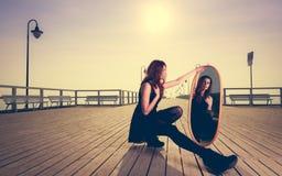 La mujer pensativa mira la reflexión en espejo Fotos de archivo libres de regalías