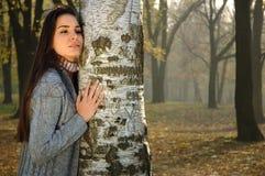 La mujer pensativa se inclinó en abedul en parque del otoño Imágenes de archivo libres de regalías
