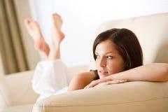 La mujer pensativa se relaja en salón en el sofá Foto de archivo libre de regalías