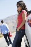 La mujer permanece en coche mientras que el hombre fija apagado para la gasolina Foto de archivo libre de regalías