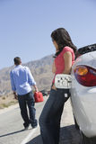 La mujer permanece en coche mientras que el hombre fija apagado para la gasolina Fotografía de archivo libre de regalías