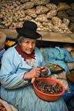 La mujer peruana pela las patatas en un mercado, Puno Imagen de archivo