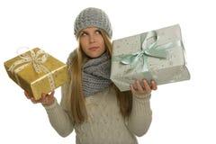 La mujer piensa en tomar una decisión entre dos regalos de Navidad Imagen de archivo libre de regalías
