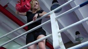 La mujer pierde la batalla y lanza lejos sus guantes de boxeo de la cólera almacen de metraje de vídeo
