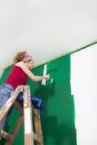 La mujer pinta el verde de la pared imagenes de archivo
