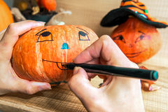 La mujer pinta la calabaza para la celebración de Halloween fotografía de archivo libre de regalías