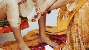 La mujer pinta las piernas del novio indio con curcumina metrajes