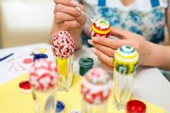 La mujer pinta los huevos de Pascua con el cepillo Imágenes de archivo libres de regalías