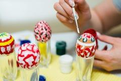 La mujer pinta los huevos de Pascua con el cepillo Fotos de archivo libres de regalías