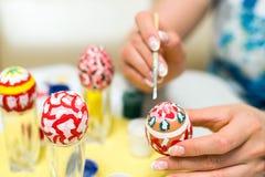 La mujer pinta los huevos de Pascua con el cepillo Imagen de archivo