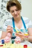 La mujer pinta los huevos de Pascua con el cepillo Fotos de archivo