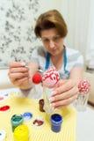 La mujer pinta los huevos de Pascua con el cepillo Foto de archivo libre de regalías
