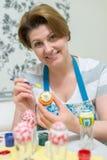La mujer pinta los huevos de Pascua con el cepillo Imagen de archivo libre de regalías