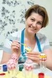 La mujer pinta los huevos de Pascua con el cepillo Fotografía de archivo