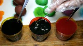 La mujer pinta los huevos de Pascua en diversos colores, sumergiéndolos en las tazas con los tintes multicolores