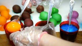 La mujer pinta los huevos de Pascua en diversos colores, sumergi?ndolos en las tazas con los tintes multicolores