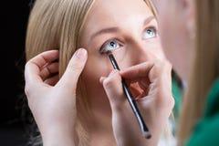 La mujer pinta los ojos de la novia fotografía de archivo libre de regalías