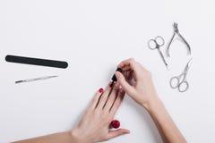 La mujer pinta sus clavos en las manos, en el accessorie de la endecha de la tabla Fotografía de archivo libre de regalías