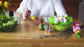 La mujer pinta un huevo amarillo en la tabla con las decoraciones de Pascua