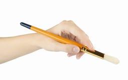 La mujer pinta una imagen con un cepillo Foto de archivo libre de regalías