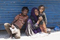 La mujer pobre india con los niños pide dinero de un transeúnte en la calle en Srinagar, la India Foto de archivo libre de regalías