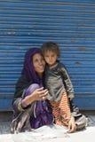 La mujer pobre india con los niños pide dinero de un transeúnte en la calle en Srinagar, la India Imagenes de archivo