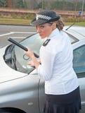 La mujer policía trata del coche gravemente estacionado Foto de archivo