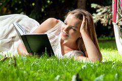 La mujer pone el libro de lectura en parque de la ciudad Fotografía de archivo libre de regalías