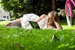 La mujer pone el libro de lectura en parque de la ciudad Fotos de archivo libres de regalías