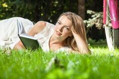 La mujer pone el libro de lectura en parque de la ciudad Imagen de archivo