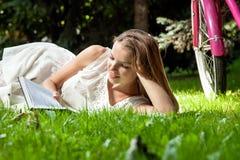 La mujer pone el libro de lectura en parque de la ciudad Fotos de archivo