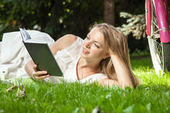 La mujer pone el libro de lectura en parque de la ciudad Foto de archivo