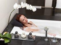 Endechas de la mujer en soapsuds en el baño. Ciérrese para arriba en un día soleado foto de archivo libre de regalías