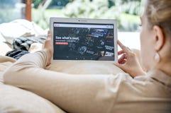 La mujer pone en marcha el uso de Netflix en la tableta de Lenovo Fotografía de archivo libre de regalías