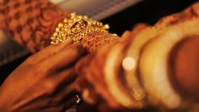La mujer pone la pulsera de oro en la pierna de la novia hindú metrajes