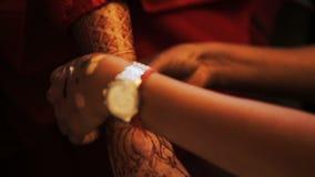 La mujer pone la pulsera lujuriante en la mano de la novia almacen de video