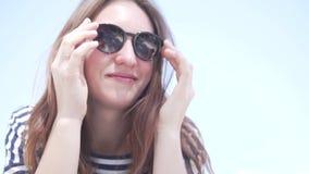 La mujer pone lentamente las gafas de sol en cara metrajes