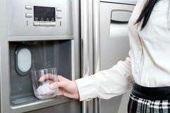 La mujer pone los cubos de hielo en el vidrio Foto de archivo libre de regalías