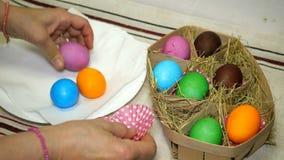 La mujer pone los huevos de Pascua coloridos en cesta con el heno
