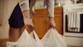 La mujer pone los paquetes en piso Primer de las manos de las mujeres puestas en bolsos pesados del piso de la comida en casa Com foto de archivo libre de regalías