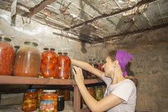 La mujer pone los tarros con las verduras y las frutas en el sótano con la comida, para el almacenamiento durante mucho tiempo Imagenes de archivo
