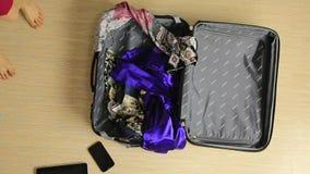 La mujer pone los vestidos en la maleta para el viaje almacen de video
