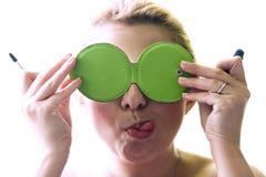 La mujer pone maquillaje y pega hacia fuera la lengua Foto de archivo libre de regalías