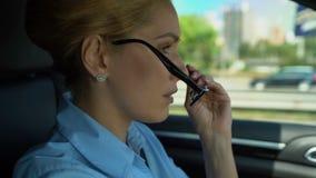 La mujer pone nervioso los vidrios mientras que conduce, las preocupaciones sobre problemas en el trabajo almacen de metraje de vídeo