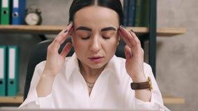 La mujer pone sus manos a sus templos debido a dolor de cabeza