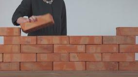 La mujer pone un ladrillo en la pared metrajes