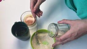 La mujer pone una cuchara de sopa de harina en un tarro de cristal Para la preparación de la levadura para el pan que cuece en ca almacen de metraje de vídeo