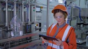 La mujer potente en la industria pesada, muchacha sonriente del obrero en casco utiliza la tableta digital para los controles y l almacen de metraje de vídeo