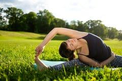 La mujer practica asana de la yoga en parque por la mañana Fotografía de archivo libre de regalías